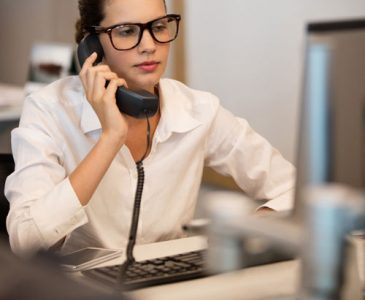 A woman in an office speaking on the phone