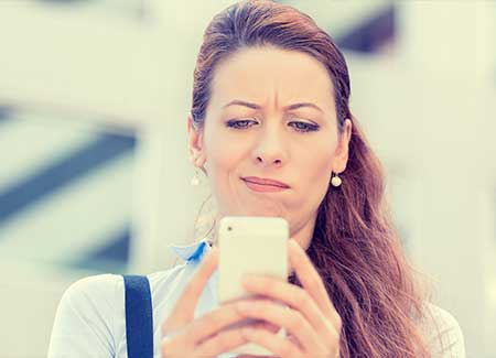 A woman looks at her mobile phone confused