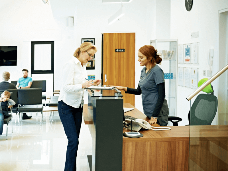A receptionist checks in a patient at the dentist