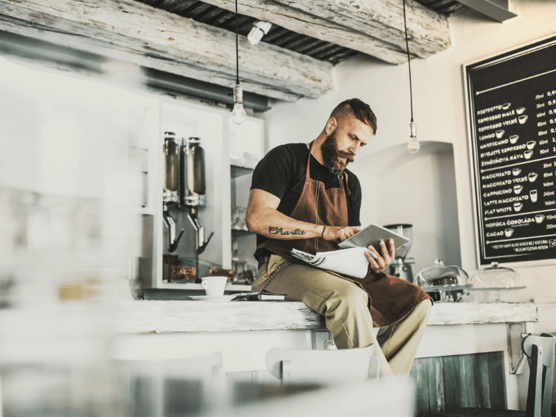 A coffee shop employee is working on taking care of the small business