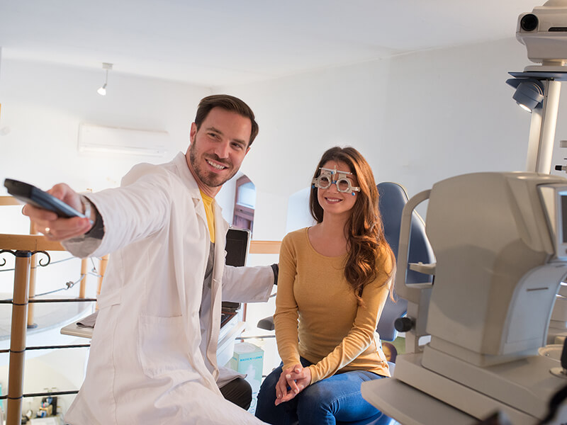 An optometrist works with a patient