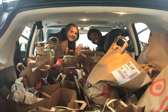 Two IC Systems employees posing with a car full of food donations