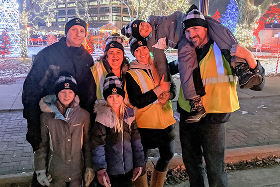 IC System Employee volunteers pose with children at the Rotary Lights display