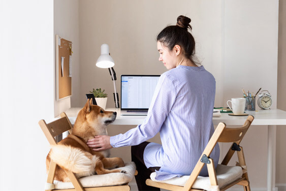 A woman petting her dog while working from home