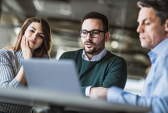 Employees gathering around a laptop