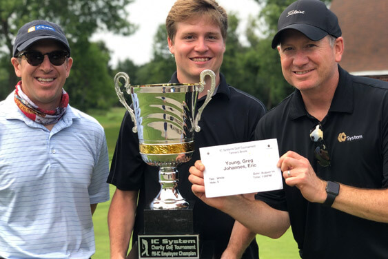 Golfers holding up their trophy and certificate at the IC Systems Annual Charity Golf Tournament