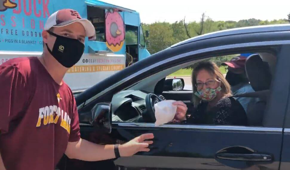 A masked IC System employee posing while giving another IC System employee food at the drive thru event