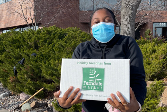 A masked IC System employer holding a thanksgiving turkey in a box gifted by IC System