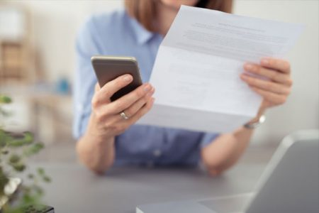 A woman is reading a letter and holding her phone