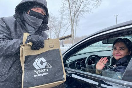 A masked IC System employee poses handing a goody bag to another IC system employee sitting in her car
