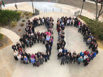 An overhead picture of IC Systems employees standing in the shape of an 80