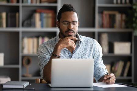 A businessman contemplating at his laptop